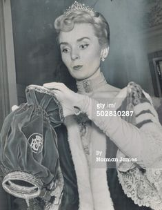 A Peeress wearing a delicate belle epoque diamond tiara to the Coronation of Queen Elizabeth II in 1953. My Grandmother, who attended that event, told me that the velvet bags were for keeping coronets in, though barley sugars and smelling salts found their way into them too.