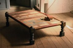 Patched, recycled wood coffee table with antique spindle legs.