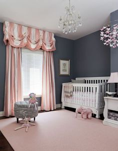 Nursery with 'needlepoint navy' walls and pink accents.