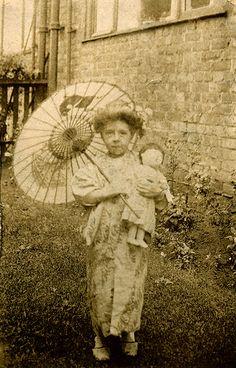 Vintage photo girl With kimono, parasol and doll