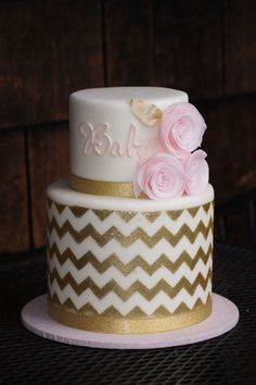 Tiered fondant covered baby shower cake with gold chevron design and pink flowers