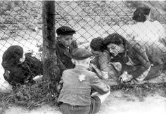 Lodz, Poland, Women and children on either side of a chain link fence in the ghetto.
