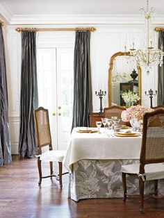 Charcoal taffeta draperies and a gray table underskirt pump up the glamour in this dining room. - Traditional Home ® / Photo: Emily Followill / Design: Lori Tippins