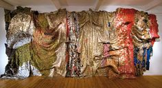 El Anatsui mostly uses aluminum seals from the tops of liquor bottles but also incorporates flattened or rolled bottle caps as well. Follow the link for more info, pics, and video.