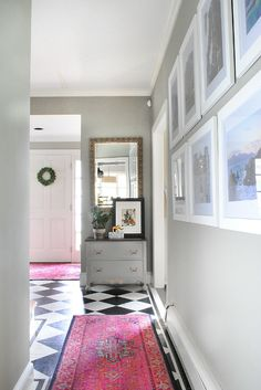 Entryway with black and white checkered floor, bold pink rugs, and vacation photos gallery wall