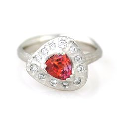 Triangular Ring featuring a 1.36 ct. prong-set trillion-cut padparadscha sapphire surrounded by 0.25 ct. tw. diamonds set in platinum with a matte redwood bark finish, $10,995; Michael Endlich at Pavé Fine Jewelry Design
