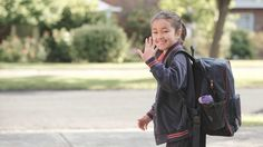 Young girl on her way to school with backpack waving hello to a friend