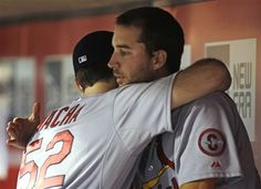 St. Louis Cardinals starting pitcher Adam Wainwright hugs Michael Wacha (52) in the dugout after Wainwright was taken out in the seventh inning of a baseball game against the Cincinnati Reds, Friday, June 7, 2013, in Cincinnati. Wainwright was the winning pitcher as St. Louis won 9-2