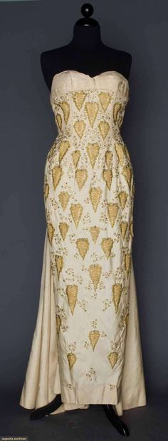 1950: JEWELED EVENING GOWN, Strapless bone silk sheath covered with beaded & tulle stylized leaves, pleated full back panel - Augusta Auctions