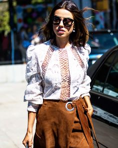 A lace blouse is paired with a suede wrap skirt and aviator sunglasses
