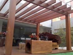 Pergolado de madeira e um ambiente com deck de madeira e móveis rusticos