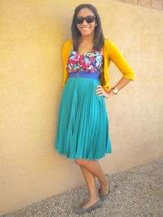 Love this pleated skirt & how her floral blouse pulls the teal & mustard colors together in a lower key color block.