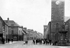 Old photograph of people on the High Street and the Steeple Clock in Kinross, Perthshire, Scotland.