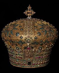 The Patriarchal Mitre of Patriarch Kyprianos (1708-09 and 1713-14). This diamond crown (Mitre) has a network of cast floral decoration studded with small diamonds, emeralds, rubies and pearls cover the entire mitre in the shape of a cross. Five repousse metal plaques represent Christ Εnthroned as the Great High Priest, above the forehead, and the busts of the four Evangelists, arranged symmetrically on the top of the mitre. Large precious stones and a cross at the top complete the…