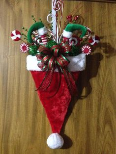 For those who think outside the box, this is a different take on the traditional Santa Hat. It would definitely look great on any door. This plush hat is filled with assorted Christmas picks, elf legs and a wired ribbon bow. May vary slightly from picture. This door hanger measures approx. 23 x 15 x 6 and is boxed for immediate shipment. Continental US shipping only.