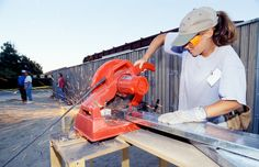 A Women Build volunteer operates the power tools at a build in Denver, CO.