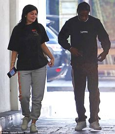 Got a lot to smile about:Travis sported Gucci track bottoms with his Supreme black and white long-sleeved top