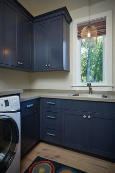 Navy cabinets are painted in Mysterious by Benjamin Moore. Wall paint color is BM Edgecomb Gray.
