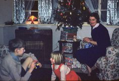 Printed colour photograph of Robin Scagell, his little sister Andrea and mother Muriel by the Christmas tree in the front room, at 1 Milverton Drive, Ickenham, Middlesex. The photograph was taken by Gordon Scagell on 25/12/1959. This is a copy made from the original colour Kodachrome transparency for the Geffrye Museum in 2009, and is one item in the Documenting Homes collection (150/2010-1 to –43) from Andrea Scagell.