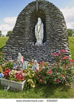 A statue of Our Lady of Lourdes in a rock grotto surrounded by nice flowers.