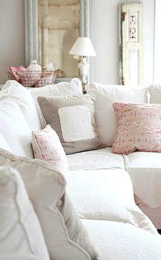 bright white shabby chic living room decor. big fluffy white pillows in linens.