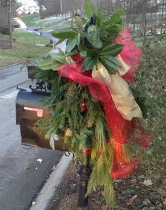 Christmas Mailbox Decoration - Lots of wonderful Evergreens and Magnolia with Pinecones and Ornaments topped off with an over-sized Red Deco Mesh Bow and Gold Ribbon.
