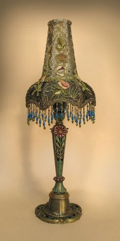 'FAIRY FLOWER' shaped shade sets upon a reticulated, candlestick style table lamp, replete with flowers, foliage and geometric design elements. The lining of the shade is dyed a bronze tone, then covered with dark gold metallic lace and overlaid with hand-embroidered silk chenille floral appliqués. Hand beaded fringe hangs from the bottom edge of the shade.
