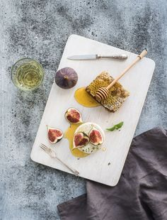 Camembert or brie cheese with fresh figs, honeycomb and glass of white wine on serving board over gr by Anna Ivanova on 500px