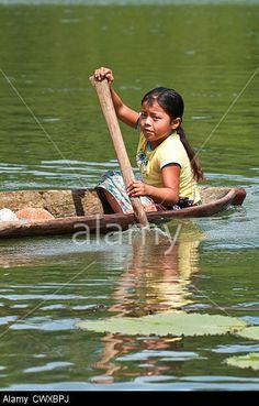 Young indigenous native indian Garifuna girl paddling a dugout canoe on Lake Izabal, Lago de Izabal, Guatemala. Stock Photo