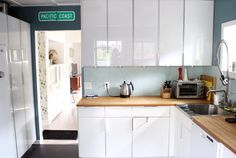 Kitchen: Shiny white cabinets with wooden counter tops