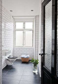 Large, clean, black and white bathroom with cool white tiles on the wall, black tiles on the floor and an old kitchen door painted in black high gloss.