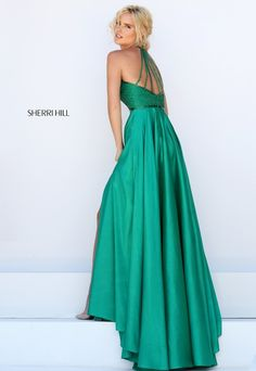 With it's long full wrap skirt in luscious jewel tones and strappy back this gown from Sherri Hill will rock any event. The details on the bodice and jeweled belt are to die for. View Size Chart