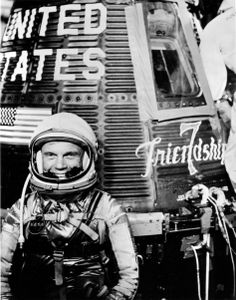 "Astronaut John H. Glenn Jr., pilot of the Mercury Atlas 6 (MA-6) spaceflight, poses for a photo with the Mercury ""Friendship 7"" spacecraft d..."