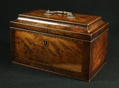 19th century flame cut mahogany tea caddy of casket form, the rectangular top with inlaid parquetry banding and crossbanded, sloping to a pl...