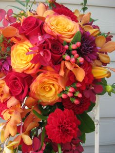 red, orange bouquet flowers using dahlias, roses, orchids, and berries