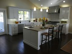 Love the dark floors with white cabinets. And the sink in the center island.