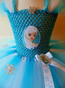 Impresionante Elsa de congelados tutús con 6 capas de alternancia de tul turquesa y blanco. (Esta es la versión más corta, hacer ya unos tambien). La tapa del ganchillo tiene un parche bordado de Elsa en el frontal, y sobre que, donde la cinta del copo de nieve de cuello halter, que es un copo de nieve de diamante. El tul tiene los copos de nieve alrededor de él y rematado con un adorno de acrílico de Elsa, con cinta de raso blanco. Viene con instrucciones de cuidado para cuidar tu tutu.