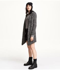 Long-sleeved, knit cardigan in bouclé yarn with wool content. Hood, side pockets, and no buttons.