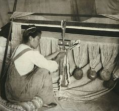 In this photograph, a woman works on a Chilkat ceremonial dance blanket using a frame loom. The warp threads, made from cedar bark covered with mountain goat wool, hang in bundles from the top bar. The weaver has completed the border on three sides and is beginning to weave the design in the center. She has carefully placed newspapers over the edges of her blanket to protect the finished portion. The newspapers originated in California and are dated January 12, 1904.
