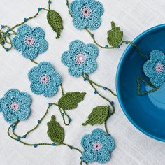 Crochet Garland Periwinkle Blue Beaded - Seven periwinkle blue flowers and six green leaves dangle from a 70 inch leaf green chain, studded with glass periwinkle beads. Each flower has a lavender center and is 2 inches across; the leaves are about 1 3/4 inches long.