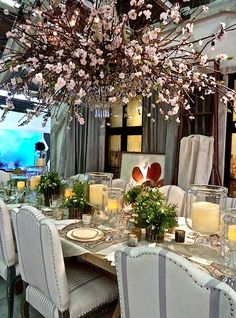 Loving the chandelier with cherry blossoms. Designed by Ralph Lauren for DIFFA Dining by Design table. Linens, striped upholstery exposed nailheads and low centerpieces with candles aglow in hurricanes. Nice rustic refined centerpiece.