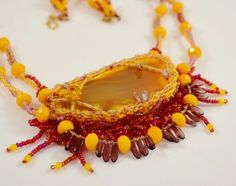"This necklace features a yellow-orange Agate center stone, embellished with Japanese and Czech Seed Beads, finished with a hand-stitched suede backing. The chain features a combination of round yellow glass beads and dark purple Czech dangles, patterned with additional Seed Beads. Length is 22"" with center stone measuring 2 1/2"" wide by 1 ¼"" long."