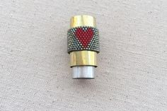 Pattern and step by step instructions to make a wide band peyote stitch beaded ring with a heart design.