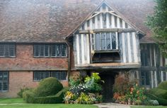 As you face the entrance side of Great Dixter, Rye, England,  the porch and everything to the right is 15th or early 16th-century, while the left hand side of the house, containing service quarters below and bedrooms above, is by Edwin Lutyens.