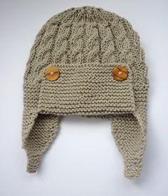 A knitting pattern for a baby aviator hat with a cable design and single button chin fastening . The pattern gives instructions for four sizes of baby hat: 0 - 3 months, 3 - 6 months, 6 - 12 months and 1 - 2 years. It is knit flat on two needles. The single cable pattern is very simple, with a six row repeat and would be ideal for someone who is trying cable knitting for the first time. **IMMEDIATE DOWNLOAD** No waiting! You will be able to download the file as soon as your payment has been…