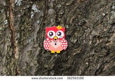 Beautiful wooden button in the shape of an owl on the background texture of tree bark. Background for cards, handmade, purple button on a wooden background. Place for text