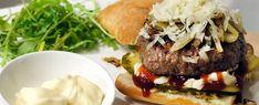 Dikke hamburger met spitskool, augurk, ui, barbecuesaus, mayo, parmezaanse kaas, met groentefrites en rucola
