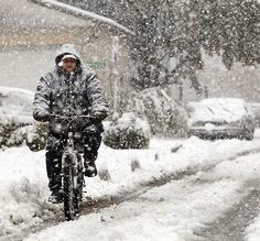 A man rides his bike down Hammaker Street, during a Halloween weekend snow storm in Highspire Saturday October 29, 2011. CHRIS KNIGHT, The Patriot-News