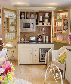 A mini-Kitchen-nette kept neatly in a small cabinet with all the necessities: fridge, micro, hotplate, sink, dishes, etc. Use of the doors as extra storage and the bottom as both mini fridge and other as potential for oven, this is excellent for a Mother-in-law garage conversion or small studio idea!