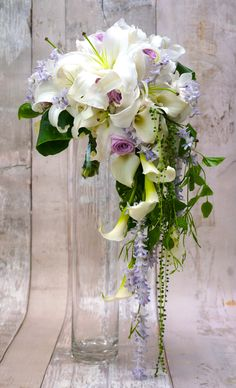 Crescent / cascading bridal bouquet with lilies, callas, hyacinth, etc. Sakie' s Floral Design